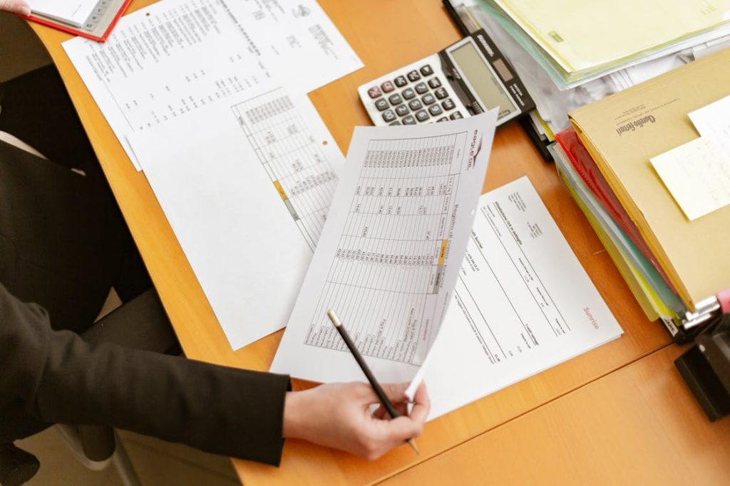 person holding paperwork, pencil and calculator at desk | Bunger Steel